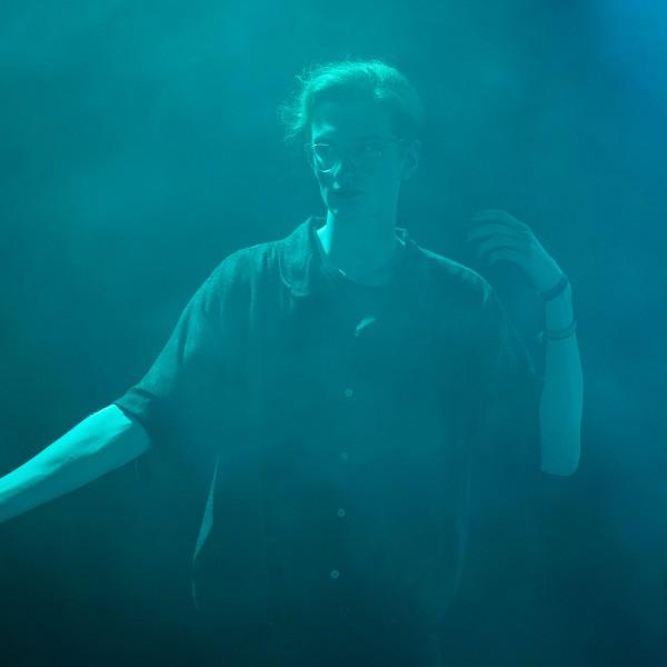 Alex, mit dunklem Lippenstift, gekleidet in ein schwarzes Hemd, steht in grün-blauem Nebel, den rechten Arm ausgestreckt.