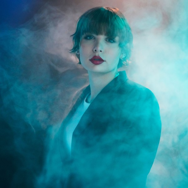 Aliée stands wearing a black blazer and white T-shirt in a green-blue fog and looks toward the camera. The lips are made up with red lipstick.