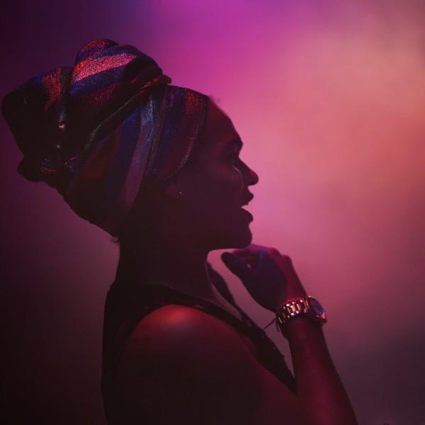 Angell Azevedo steht mit glitzernder, gewickelter Kopfbedeckung im Profil zur Kamera in einem dunklen, lila nebligen  Raum, ihre Hand am Kinn.