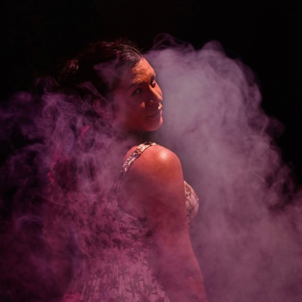 Bruna stands in a cloud of purple fog in a dark room and looks over her shoulder.