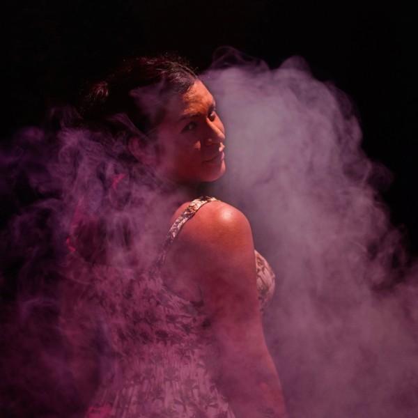 Bruna steht in einer lila Nebelwolke in einem dunklen Raum und blickt über die Schulter.