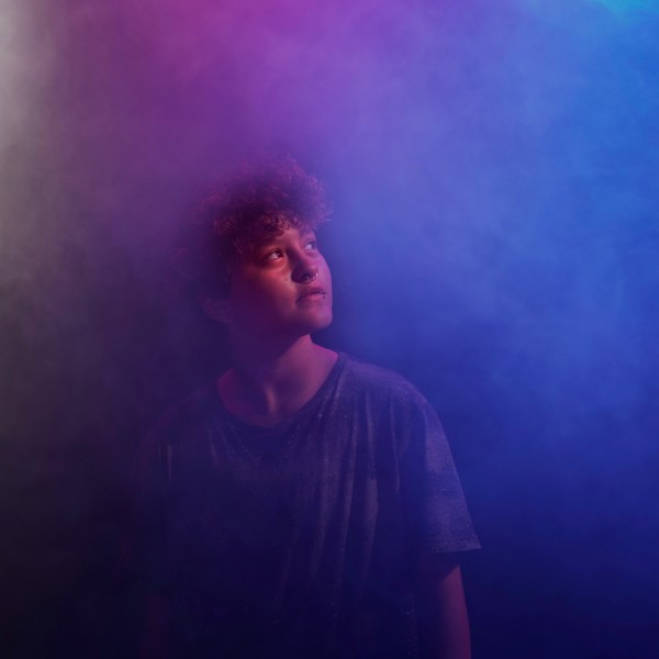 Ethan stands surrounded by a thick purple-blue fog in a dark room and gazes upward and left.