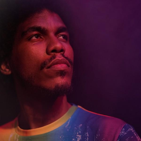 Bruni steht in einem Regenbogen Tshirt in einem dunkel lila Raum und blickt nach rechts oben.