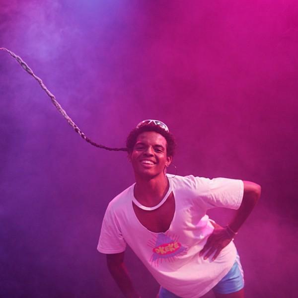 Joana steht gebückt in einem lila nebligen Raum und wirft einen einzelnen, an die kurzen Haare geflochtenen Zopf in die Höhe.