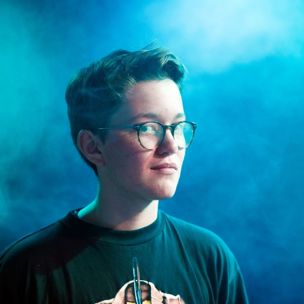Jonathan mit kurzen braunen Haaren und Brille in einem blau nebligen Raum blickt in die Kamera.
