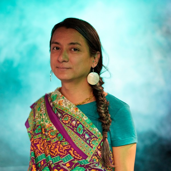 Kamalanetra stands in a turquoise blue foggy room and looks toward the camera. Her long hair hangs in a braid over her left shoulder. She wears a colourful  sari and large silver earrings.
