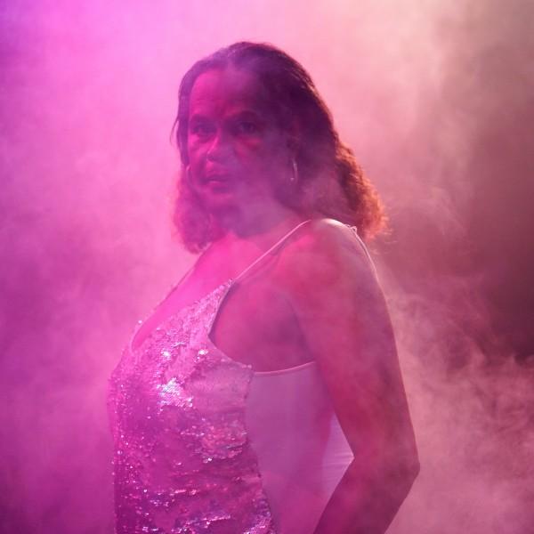 Karla steht mit schulterlangen, gelockten Haaren und einem gold glitzernden Top in einem lila nebligen Raum seitlich zur Kamera und blickt zu uns.