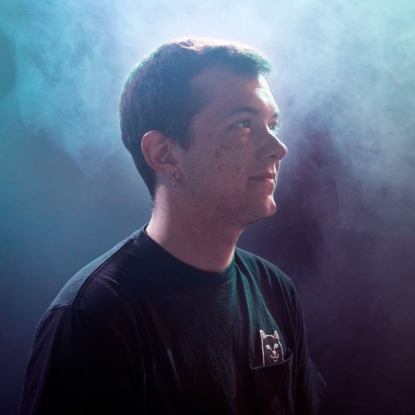 Lenny stands in profile looking to the left in a dark blue foggy room with short brown hair wearing a black T-shirt.