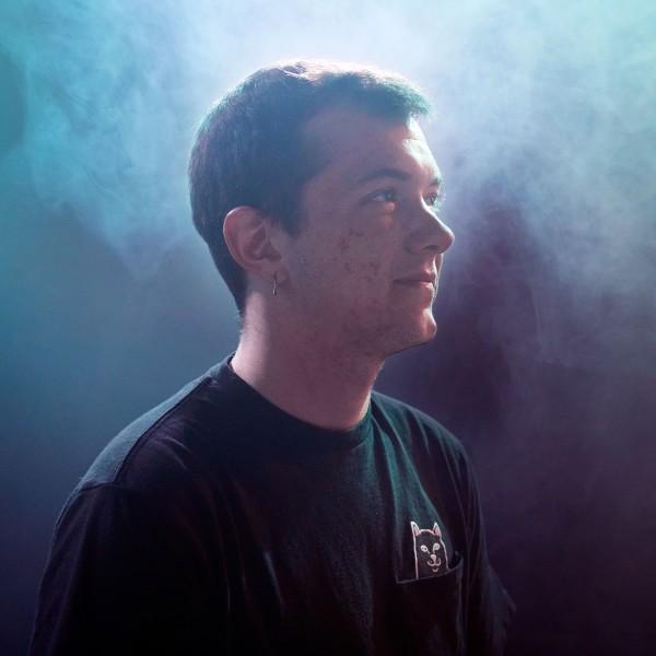 Lenny steht mit kurzen, braunen Haaren und schwarzem T-Shirt im Profil zur Kamera in einem dunklen Raum mit blauem Nebel.