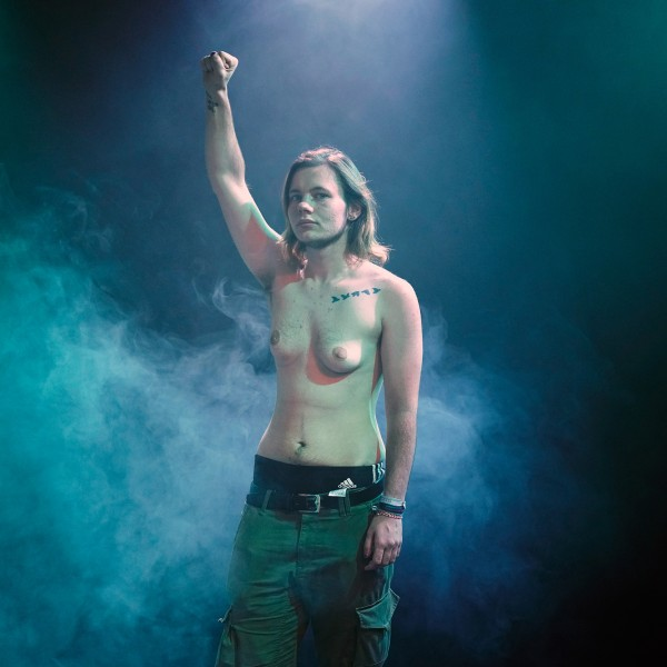 Luke steht oben ohne in einem dunkelvioletten, nebligen Raum mit schulterlangem, blondem Haar und hochgehaltener rechter Faust.
