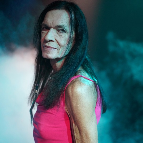 Michi stands in profile in a dark turquoise foggy room and looks over their left shoulder toward the camera. Michi wears a sleeveless pink top and has long black hair.