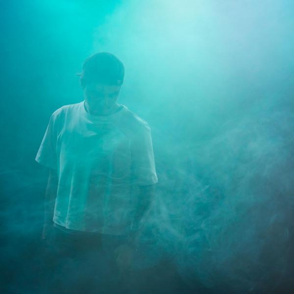 Nino steht auf den Boden blickend und von dickem türkisblauem Nebel verdeckt,er  trägt ein weißes T-Shirt.