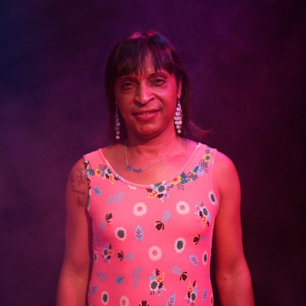 Pâmela stands in a dark purple foggy room looking straight into the camera wearing a pink dress and long glittery earrings.