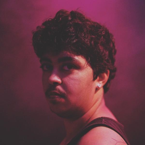Pedro steht in einem dunkelvioletten, nebligen Raum und dreht den Kopf über seine linke Schulter in Richtung Kamera. Er trägt einen silbernen Ohrring und ein schwarzes Westenoberteil.