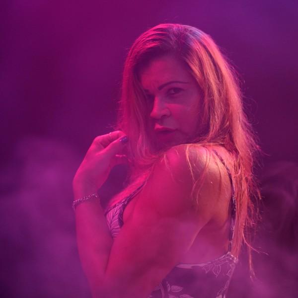 Ranella steht im Profil, ein Kleid mit schmalen Schulterriemen tragend, in einem dunkelvioletten, nebligen Raum mit langen blonden Haaren und schaut über ihre linke Schulter in die Kamera.