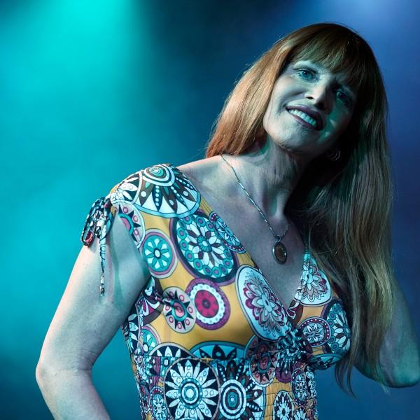 Claudia steht mit rötlichen, brustlangen Haaren in einem Blumenkleid in einem blau nebligen Raum.