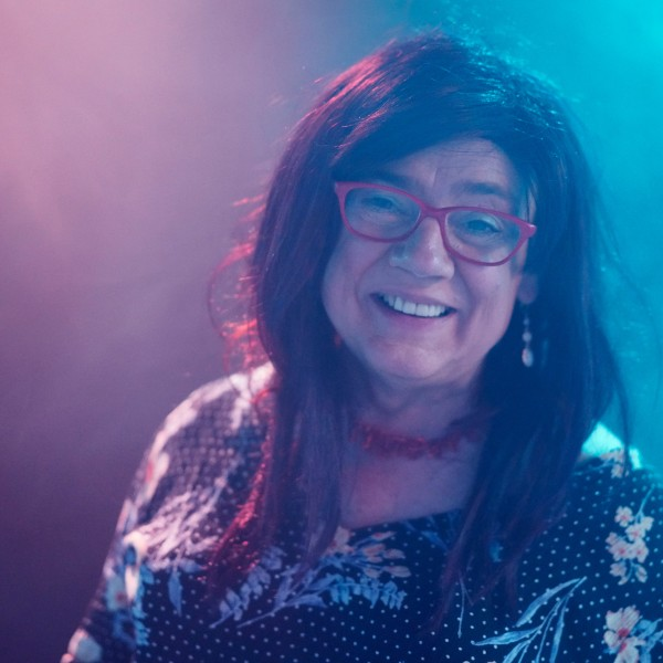 Sonja Elaine steht lächelnd mit rotbraunem Haar in einem türkisvioletten Nebelraum, trägt eine Brille, eine rote Halskette und ein blumiges Kleid.