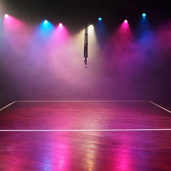 Ein dunkler, menschenleerer Raum mit einer Mischung aus rosa-blauen und weißen Theaterlichtern, die Nebelwolken erhellen. Die Lichter spiegeln sich auf dem Holzboden. Die Bodenlinien für eine Mannschaftssportart sind auf dem Boden mit weißem Klebeband markiert. In der Mitte des Raumes hängt eine 360-Grad-Kamera.
