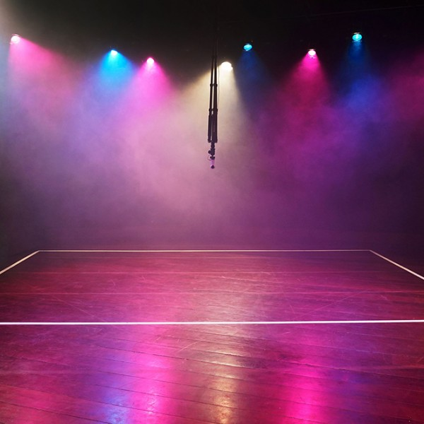 A dark room empty of people with a mixture of pink blue and white theatrical lights that are illuminating clouds of fog. The lights are reflected in the wooden floor. The boundaries for a team sport are marked out on the floor with white tape. Hung in the middle of the room is a 360 degree camera.
