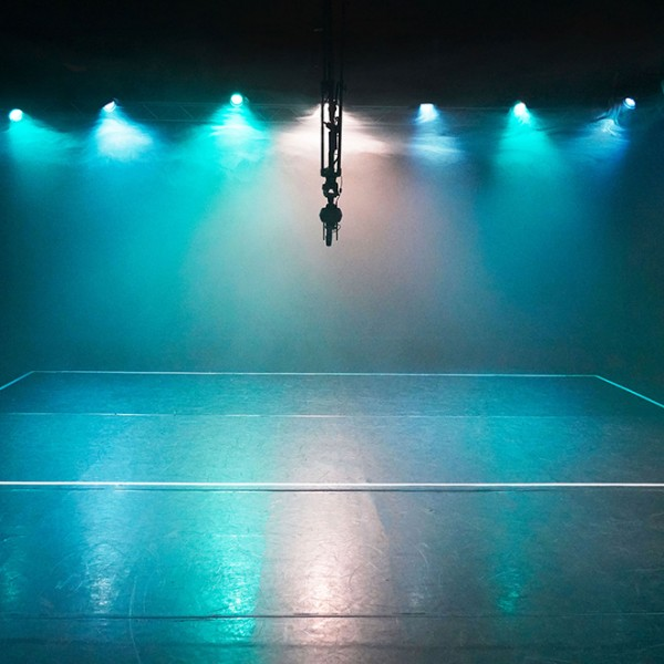 A dark room empty of people with a mixture of turquoise, blue and white theatrical lights that are illuminating clouds of fog. The lights are reflected on the floor. The boundaries for a team sport are marked out on the floor with white tape. Hung in the middle of the room is a 360 degree camera.