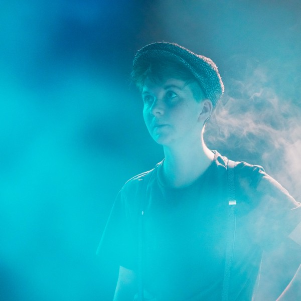 Tjark stands immersed in a blue purple fog wearing a flat cap, T-shirt and braces looking upward and to the right.
